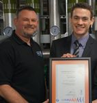 CRC Operations Manager Mark Neville, left, is presented with the college's ISO accreditation by Stephen Davies of Systems & Services Certification.