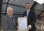 Mark Swales receiving the certificate from Stephen Hudson on the roof of the Cantor Building